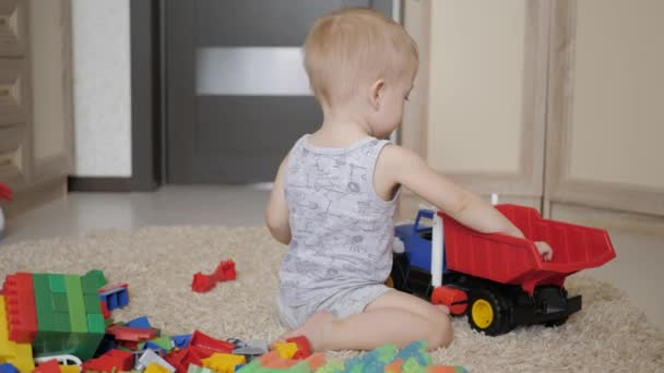 Lovely baby boy playing with a big car toy on floor at home. Kid boy toddler playing with toy car indoors. Future driver. Funny toddler boy indoors.