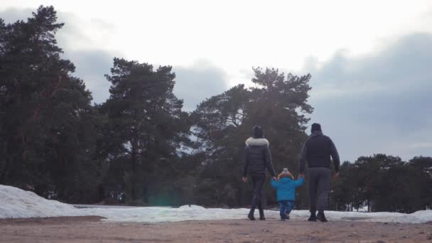 Happy family walks in winter forest. Parenthood, season and people concept.
