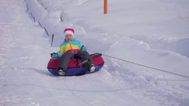 Young girl riding on inflatable snow tube from a hill.