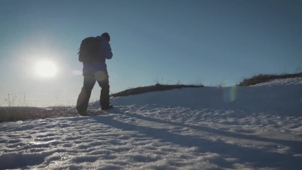 Backpacker walking on snow mountain in winter. Man with backpack trekking in mountains. Winter hiking.
