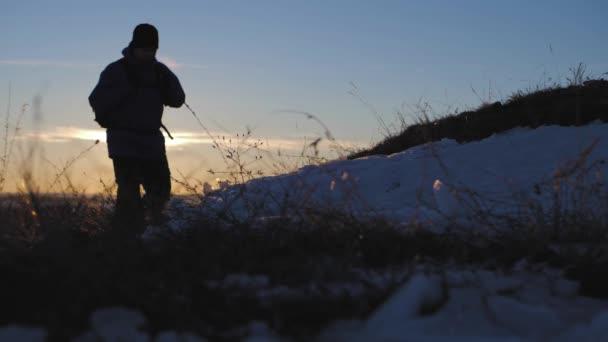 Backpacker walking on snow mountain in winter. Man with backpack trekking in mountains. Winter hiking.
