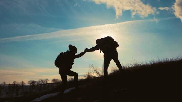 Několik turistických pomoci navzájem silueta v horách. Týmová práce pár Turistika, vzájemně si pomáhat, důvěřovat pomoc, západ slunce. Muž dává ruku ženě pomoci jí lézt na horu