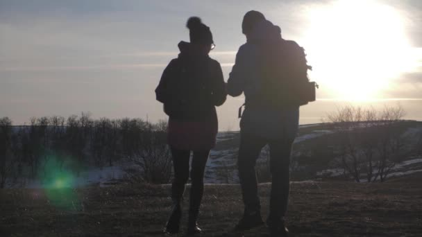 Happy couple man and woman tourist at top of mountain at sunset outdoors during a hike. Silhouettes of two hikers with backpacks enjoying sunset. The concept of travel and active lifestyle.