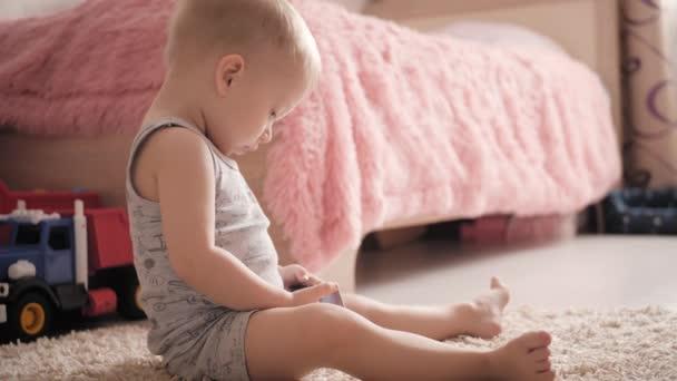 kleiner Junge schaut Cartoons auf dem Smartphone zu Hause auf dem Fußboden, Lifestyle.