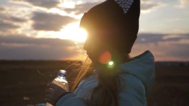 Kleines Mädchen trinken frische Wasser aus Kunststoff-Flasche mit Sonnenuntergang Hintergrund. Gegen den Durst