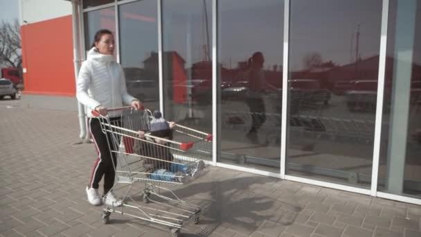 Ragazzo sorridente sveglio che si siede in carrello di acquisto. Famiglia felice va a fare shopping.