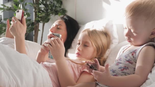 Young mother, daughter and little son are using gadgets lying on a white bed. Concept modern family during weekend at home. Contemporary technology.