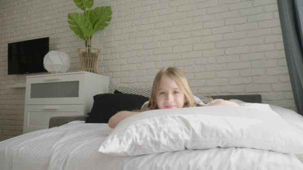 Happy girl child waking up on the bed in the morning. Health, beauty and childhood concept.