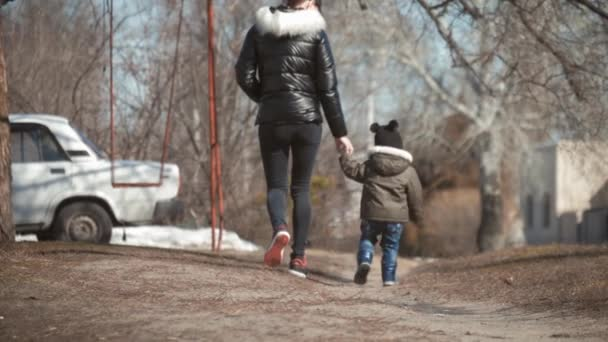 Mother and her little son on walk holding hands, concept of motherhood and childhood.