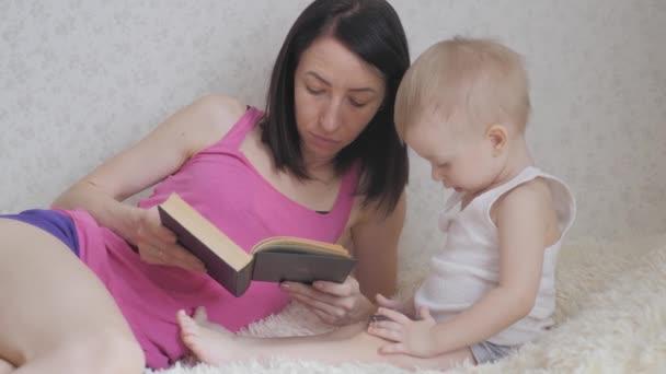 Šťastný matka čte knihu dítě chlapci uvnitř. Sladké chvíle s knihou čtení matka s dítětem.