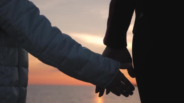 Silhouette of mothers and daughters walking on the beach while holding hands with sunset background. Close up on silhouette of couples arms holding hands at sunset by the sea.