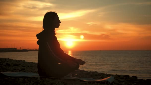 Silhouette of young beautiful healthy woman meditating in lotus position by the sea at sunset. Young woman practicing yoga outdoors. Harmony and meditation concept. Healthy lifestyle.