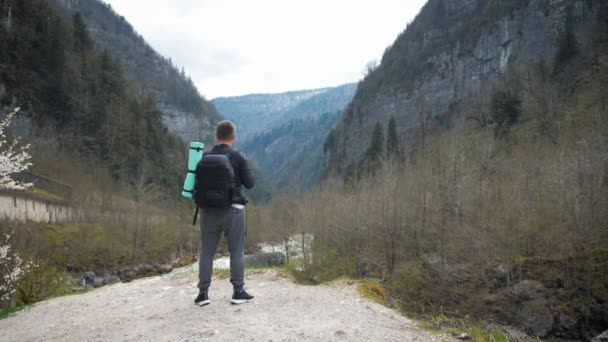 Man tourist hiker with backpack enjoying scenic view mountain river landscape. Travel hiker looking away. Travel, people and lifestyle concept.