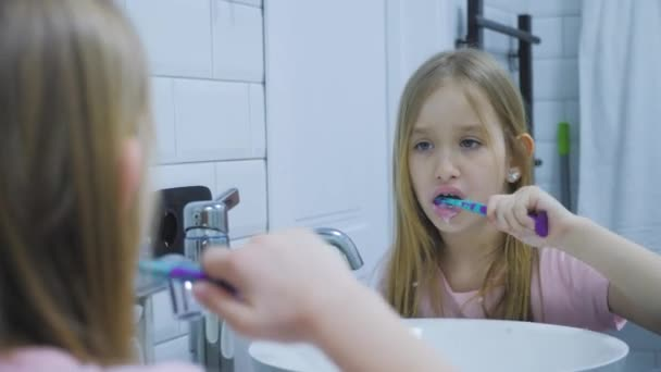 Pre teen girl brushes her teeth and washing his face in the bathroom.
