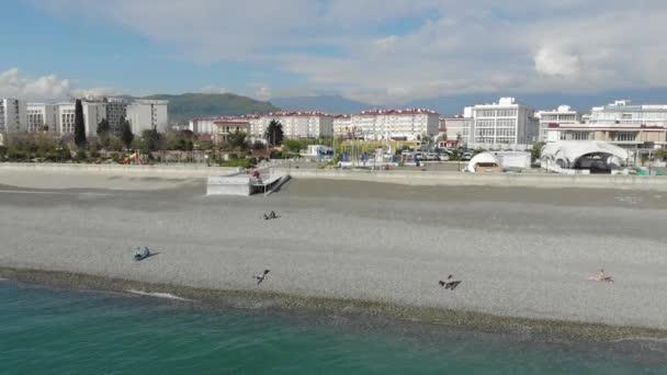 Légifelvételek az emberek tömeg pihentető tengerparti és tengeri hullámok. Felülnézet a repülő drone.
