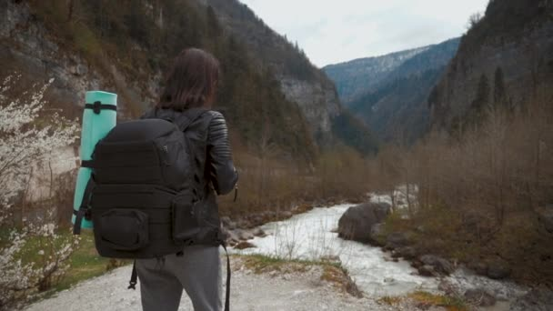 Lady hiker with backpack looking on hills and mountain river lake, girl enjoying nature panoramic landscape in trip, relax holiday. Traveler woman exploring woods. travel and wanderlust concept.
