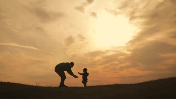 Silhouettes father and little son playing on the meadow at the sunset time. Concept of friendly family.