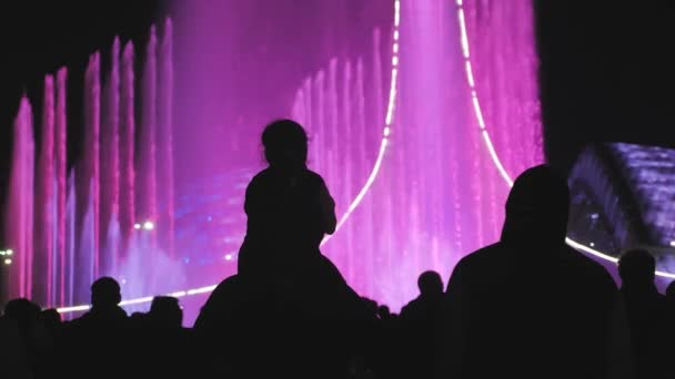 Silhouettes of people who are watching and taking photos the bright color fountain. People take a photo of the light and music fountain show.