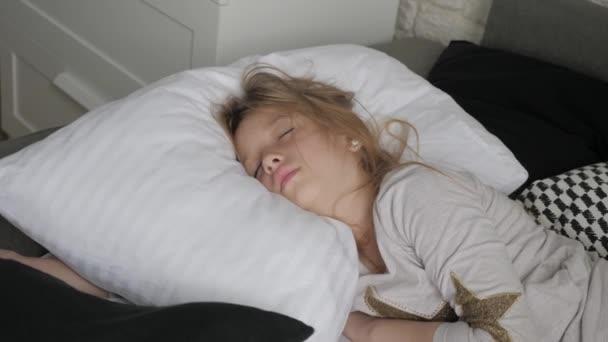 Šťastné dívčí dítě, které se ráno probouzí na posteli. Koncepce zdraví, krásy a dětství.
