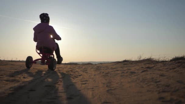 Silhouette of a girl on a bicycle and little brother on the background of sunset. Children having fun a bicycle in the sunset light.