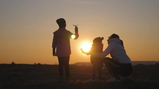 Little girl playing with a paper airplane, mom and little brother are looking at her. Silhouette of mother and two children at sunset. Concept of dreams and travel.
