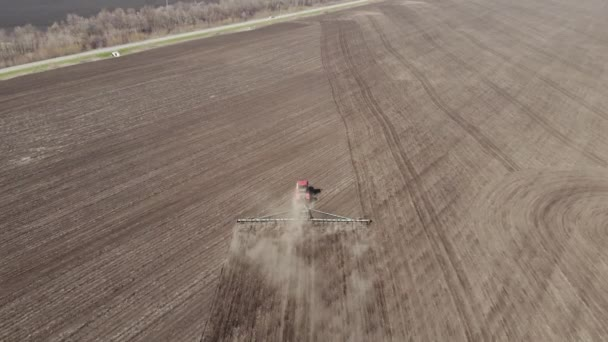 4K Aerial footage modern red tractor on the agricultural field on sunny day. Tractor plowing land. Tractor cultivating field at spring.