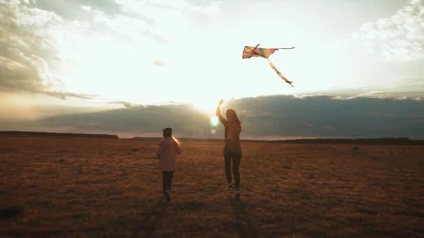 glückliche Familienmutter und ihre kleine Tochter lassen bei Sonnenuntergang einen Drachen auf der Wiese steigen. Lustige Familienzeit. Konzept freundlicher Familie, Reisen und Freiheit.