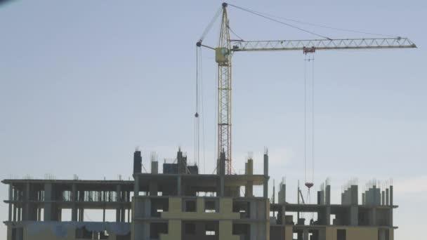 Stavba s časovou konstrukcí jeřábu zvednutím betonového montážního panelu na montážní budovu. Jeřáb zdvihá těžký náklad na staveništi.