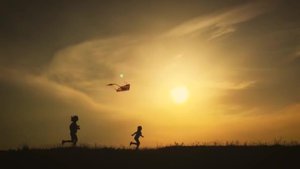 Šťastná rodinná matka a dětská dcera při západu slunce odpálení draka na louce. Legrační rodinný čas. Koncepce přátelské rodiny, cestování a svobody.