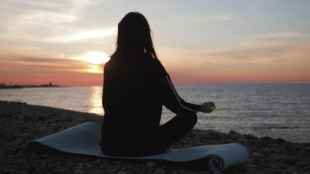 Silueta mladé, krásně zdravé ženy meditující v lotosové poloze u moře při západu slunce. Mladá žena trénuje jóga venku. Koncepce harmonie a meditace. Zdravý životní styl.