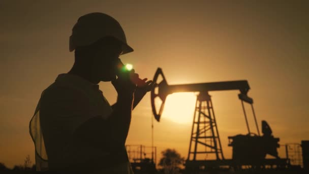 Silueta mužových inženýra s telefonem, který dohlíží na místo produkce ropy při západu slunce.