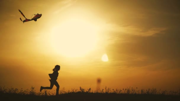 Felice famiglia madre e figlia bambina lanciare un aquilone sul prato al tramonto. Divertente tempo in famiglia. Concetto di famiglia amichevole, viaggi e libertà.