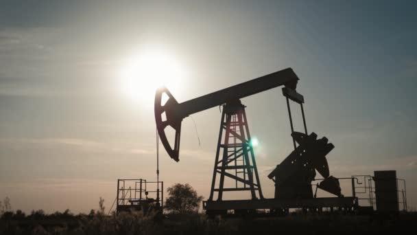Napnyugtakor olajszivattyú sziluettje az olajmezőn. Az ipari berendezések.