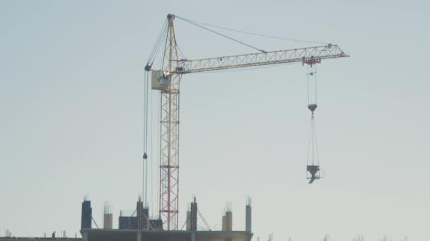 Kran und Baustelle vor blauem Himmel. Hochbau mit Schalung.
