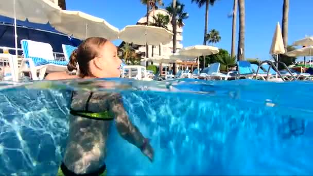 Happy girl playing in outdoor swimming pool on summer vacation on tropical beach.