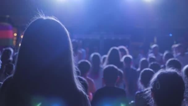 Na diskotéce v průběhu laserové show s paprskovým osvětlením se nachází dětské siluety. Rozmazaný noční klub děti baví se hudbou tančící zvuk.