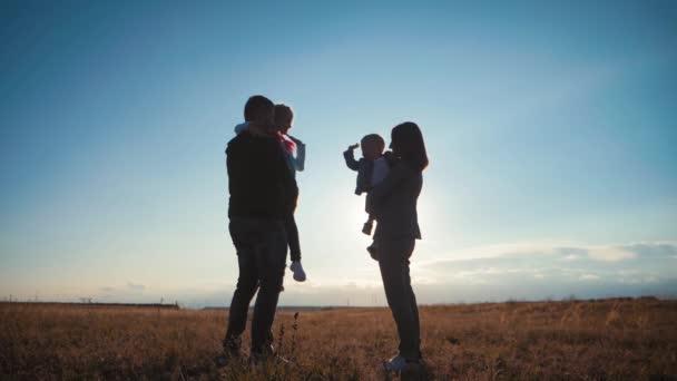 Una silhouette felice giovane famiglia. Felice famiglia al tramonto. Padre, madre e due bambini divertirsi e giocare nella natura. Concetto di famiglia amichevole e di vacanza estiva.