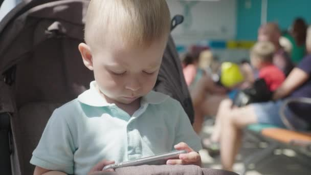 Baby boy child watching a video from smart phone. Kids playing with smartphone. leisure, children, technology, internet addiction. Child is watching a cartoon on a mobile phone.