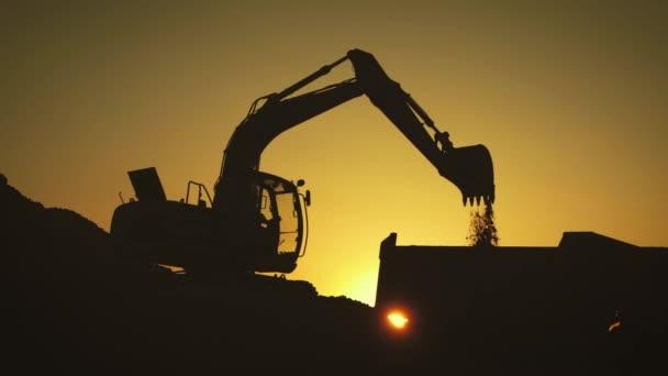 Silhouette eines Baggers, der bei Sonnenuntergang Sand in einen LKW lädt. Konzeptbau und Schwerindustrie, Maschinen werden in der Schwerindustrie eingesetzt. Zeitlupenaufnahmen.