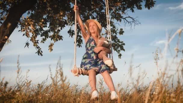 Boldog vicces lány kalap játszik egy mackó a kötél hinta alatt naplemente. Kid játszik a természetben a szabadban. Gyönyörű napsugarak. Gyermekkori álmok.