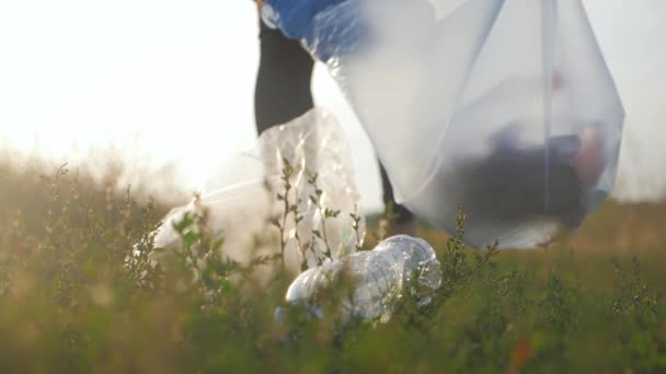 Törődnek a természettel. Önkéntes lány összegyűjti szemetet a szemetet zsákba. Trash-mentes bolygó fogalmát. Természettakarítás, önkéntes ökológia-zöldes koncepció. Környezeti műanyag szennyezés.