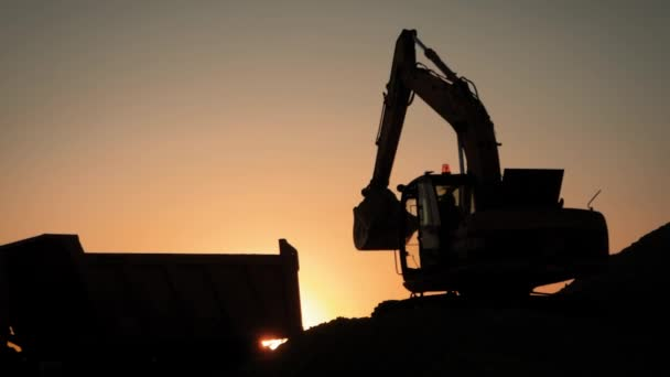 Silhouette of an excavator that loads sand into a truck at sunset. Concept construction and heavy industry, machine will be used in heavy industry business. Slow motion footage.