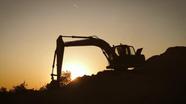 Silueta bagru, který při západu slunce nakládá písek do náklaďáku. Koncepce stavebnictví a těžkého průmyslu, stroje budou použity v těžkém průmyslu podnikání. Zpomalený záznam.