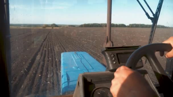 Farmer driving tractor in cultivating field. Agricultural works at tractor.