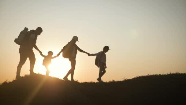 Rodiče a dvě děti procházející se po horách v době západu slunce. Silueta šťastná krásná rodina během cestování. Koncept přátelské rodiny a cestování.