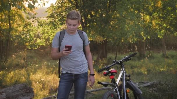 Chlapec v parku po jízdě na kole používá telefon při západu slunce a sleduje společenské sítě nebo chatování. Koncept zdravého životního stylu ve městě.
