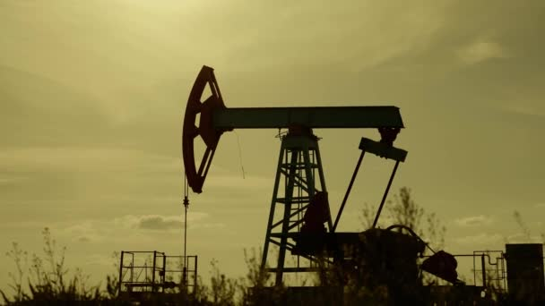Silhouette of working oil pump from oil field at sunset. The industrial equipment.