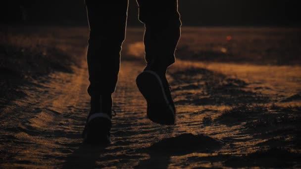 Běžící mužská silueta v čase západu slunce. Venkovní běh na běžkách. Atletický mladík běhá v přírodě během zlatého západu slunce. Zdravý životní styl.