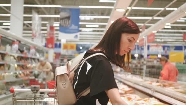 Mladá žena nakupuje zdravé jídlo v supermarketu. Prodej, nakupování, konzumní a koncepce lidí.