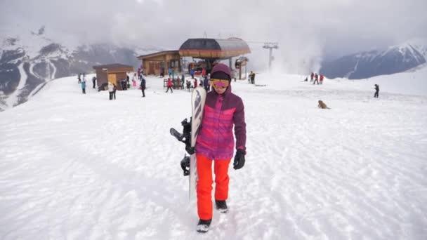 Dívka snowboardista se snowboardem na vrcholu hory na lyžařském středisku. Zimní sporty a zimní dovolená koncept. slunečný zimní den v lyžařském středisku.